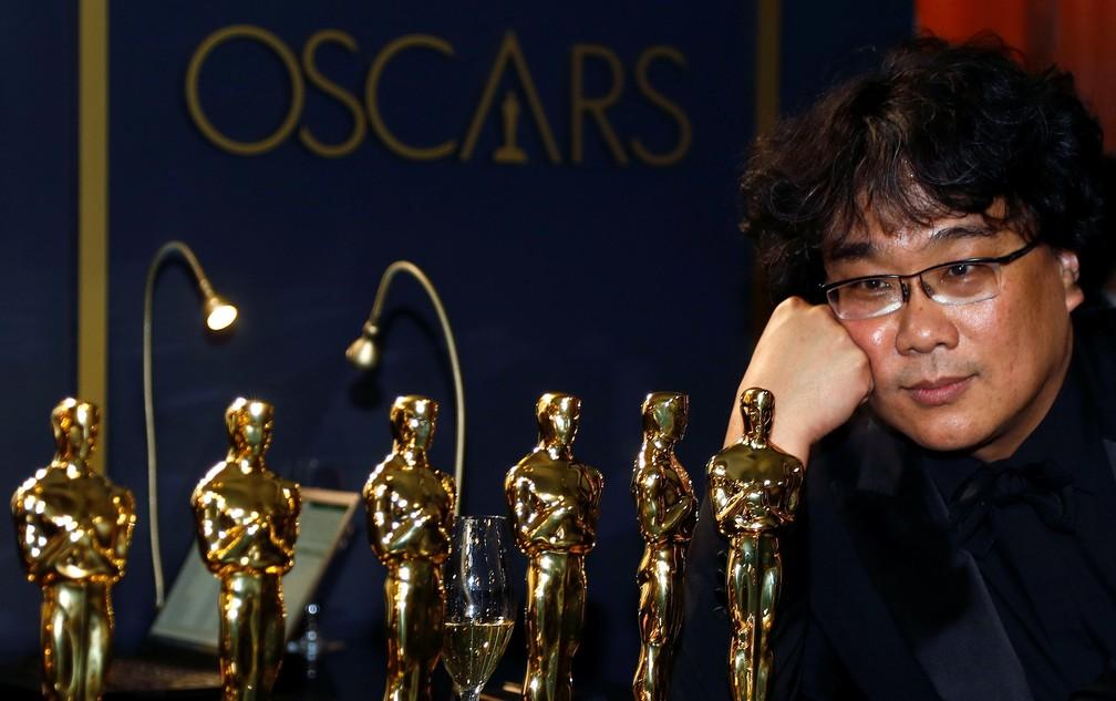 Bong Joon-Ho admira as estatuetas que ganhou no Oscar 2020 — Foto: Eric Gaillard/Reuters